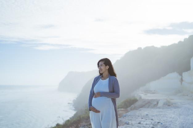 Беременная мама стоит рядом со скалой