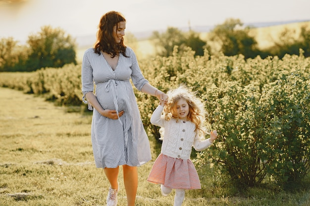 Pregnant mother with her daughter in a field