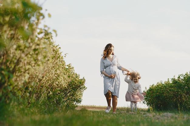Беременная мать с дочерью в поле