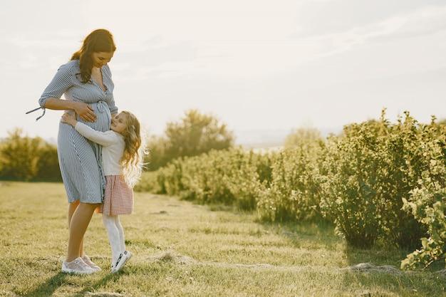 필드에 그녀의 딸과 함께 임신 어머니