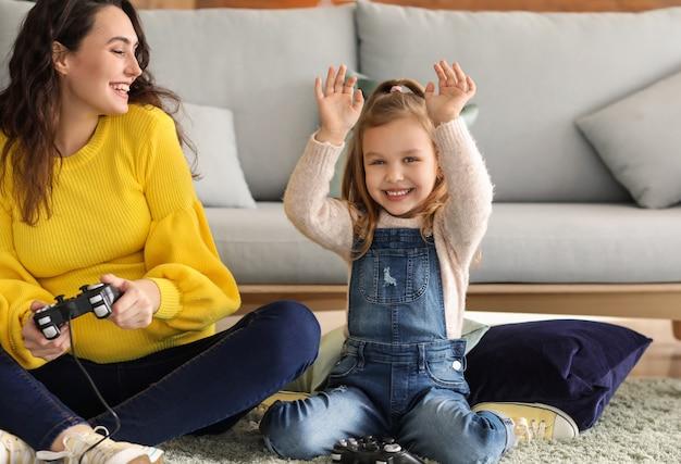 집에서 비디오 게임을하는 작은 딸과 함께 임신 어머니