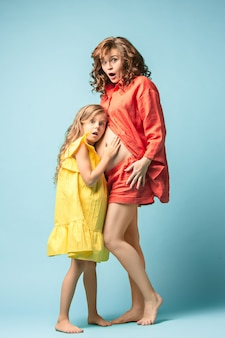 Pregnant mother with teen daughter. family studio portrait over blue wall