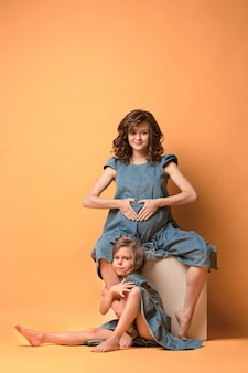 Pregnant mother with teen daughter. family studio portrait over brown wall