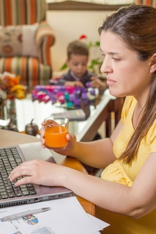 Беременная мать, работающая в домашнем офисе с сыном