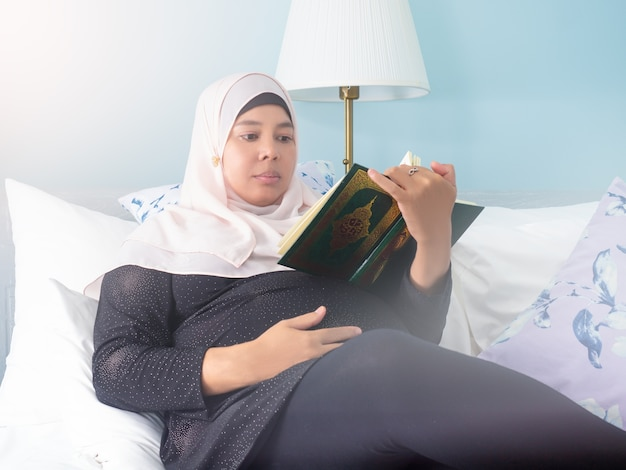 Pregnant muslim woman reading a book on her hand with smile face. maternity