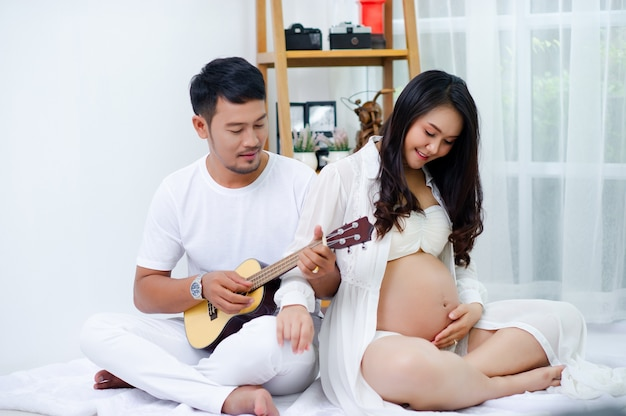 Pregnant people are enjoying their husbands, singing songs for their children with love.