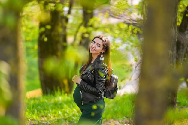 妊娠中の女子高生。路上でポーズドレス女子高生の魅力的な妊娠中の女性。大学の妊娠、通りを歩いて長い髪の妊娠中の女性