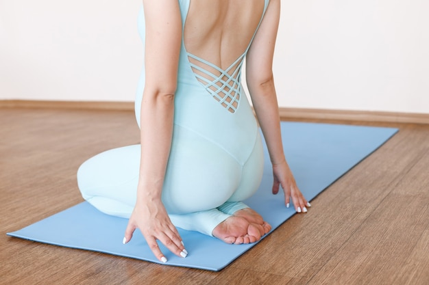 妊娠中の人は、明るい背景のスポーツマットに背を向けて座っています。閉じる。妊娠中の女性のためのヨガ