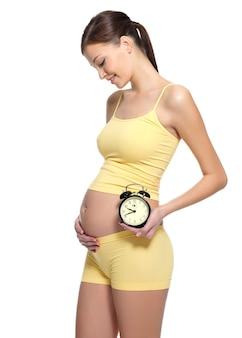 白で胃の近くに時計を保持している妊娠中の笑顔の女性