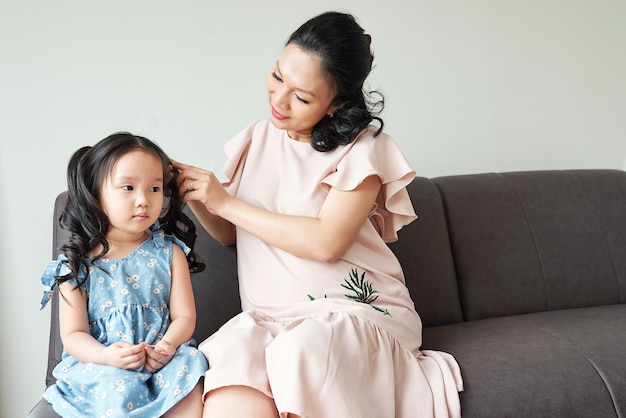 Pregnant vietnamese young woman braiding hair of her serious little daughter when thay are getting ready in the morning