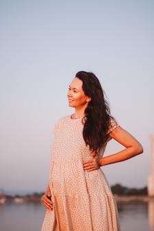 自然を背景に妊娠中の女性長い黒髪の美しい若いアジアの女性がポーズをとる...
