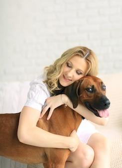 Беременная женщина и собака сидят на диване мило обнимаются