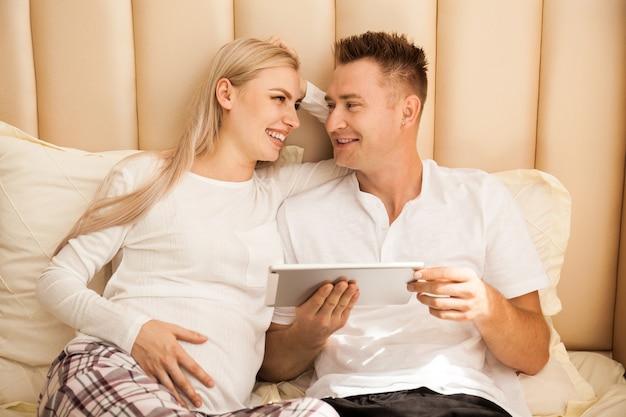 妊娠中の女性と自宅のベッドに横になっている男