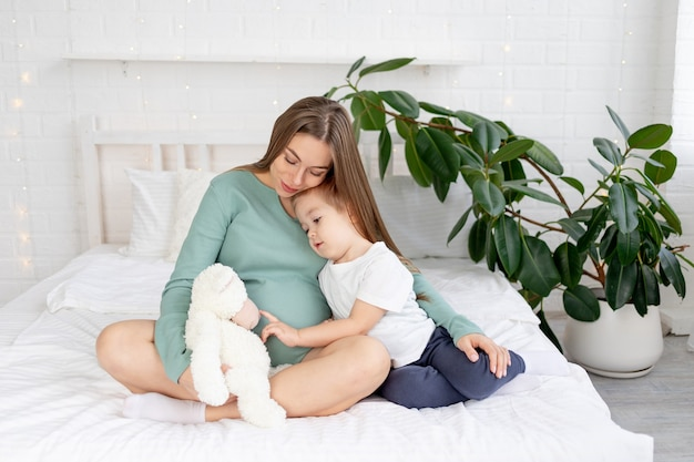 임신한 여자와 아기 아들이 집에서 큰 배를 만지고 침대에서 껴안고, 임신의 개념과 가족 중 아기와 두 번째 아이의 탄생을 기다리는 것