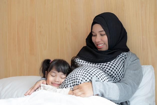 Беременная женщина и ее дочь, держась за руки на живот на кровати