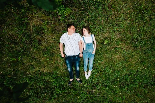Беременная женщина и ее муж счастливы лежать на траве на открытом воздухе. вид сверху.