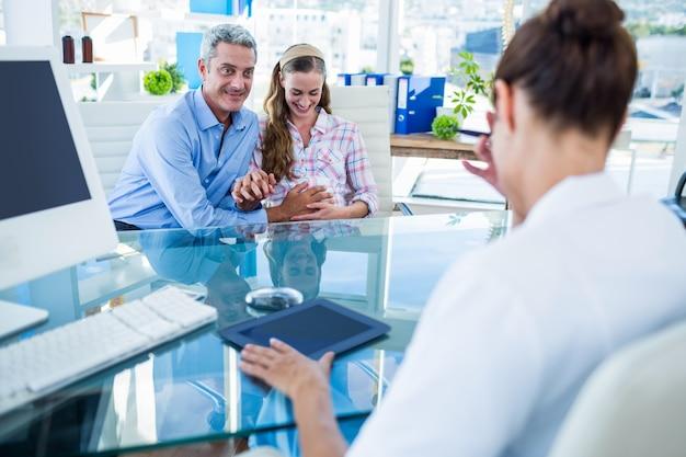 Беременная женщина и ее муж обсуждают с врачом