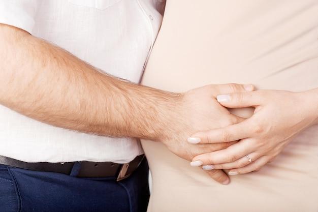 妊娠中の女性と彼女の夫が妊娠中の腹に手を繋いでいます。