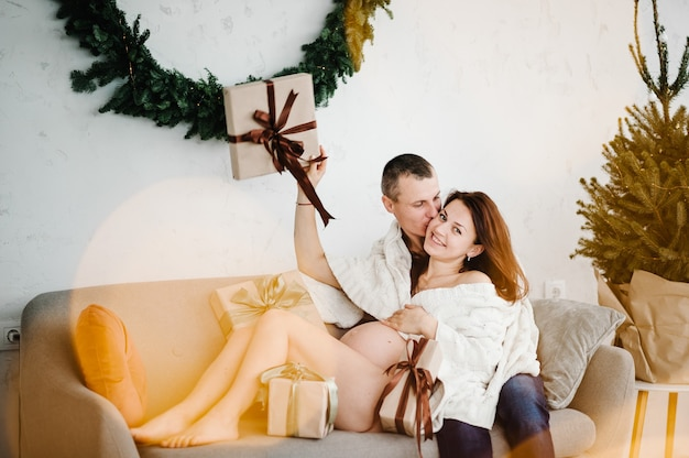 妊娠中の女性と男性が自宅のクリスマスツリーの近くに格子縞で覆われていますメリークリスマス