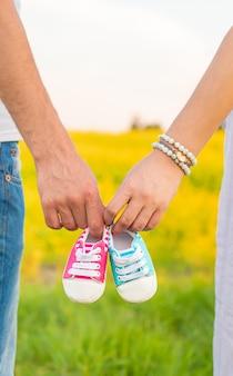 Беременная женщина и мужчина держат детскую обувь.