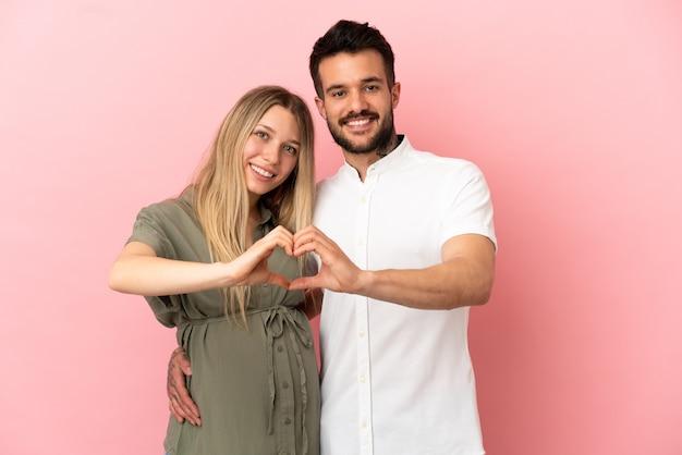 임신한 여자와 남자는 손으로 하트를 만드는 고립된 분홍색 배경 위에