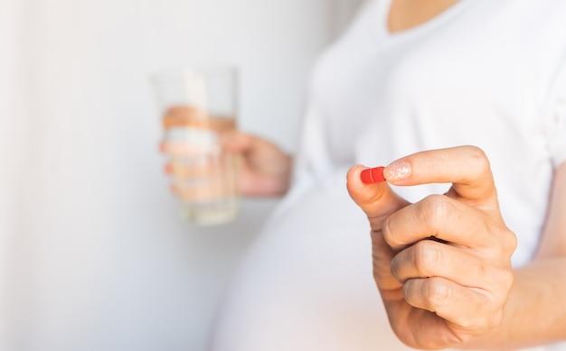 Беременная женщина принимает и ест витаминные лекарства и пьет воду, чтобы питать беременность. концепция здравоохранения образ жизни.