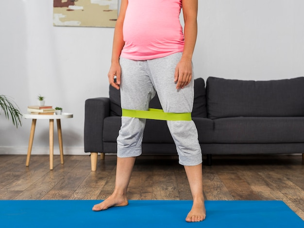 Беременная женщина дома упражнения с резинкой