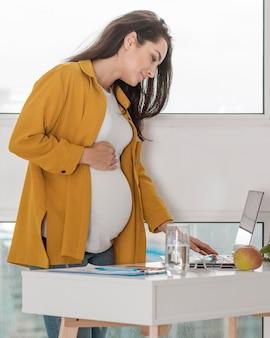 Беременная женщина дома работает на ноутбуке