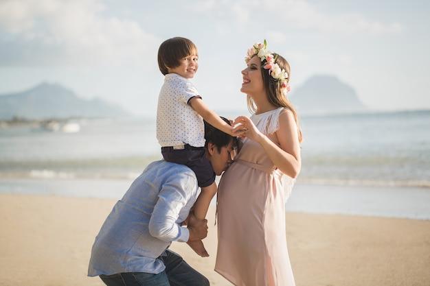 임신 한 여자, 아기와 해변에서 혼혈 남자