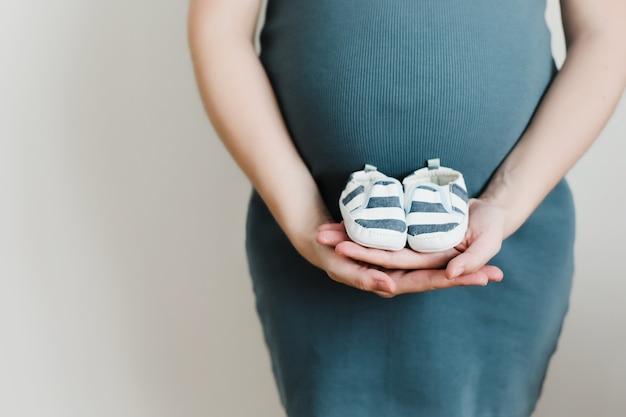 아기 옷과 임신 한 여자 배