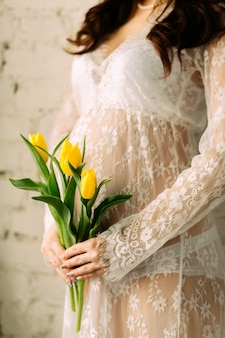 Pregnant woman belly with tulip flowers