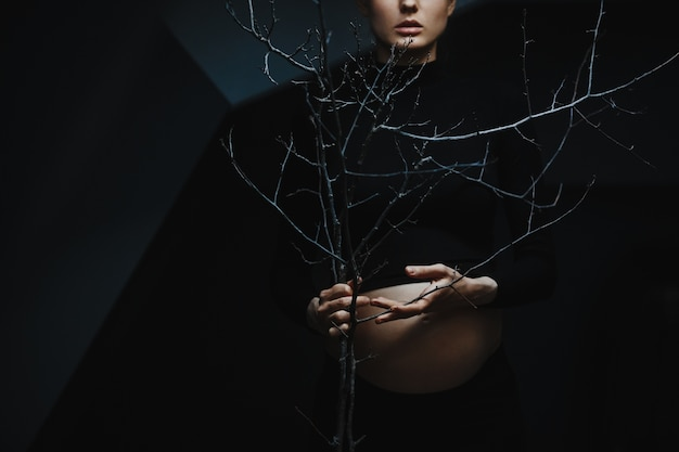Pregnant woman in black clothes stands under grey wall and holds a tree branch