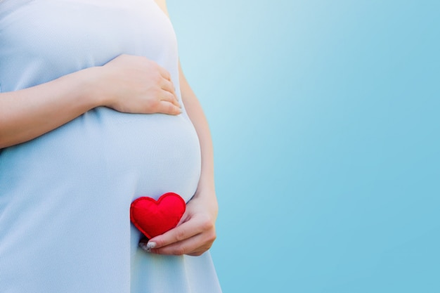 A pregnant woman in a blue dress holds in her hands a red heart on blue. pregnancy concept