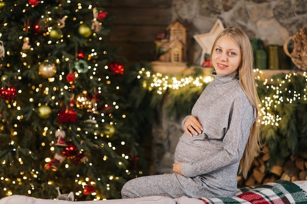Беременная женщина, лаская живот возле елки и камина
