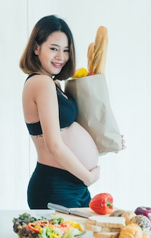 Pregnant woman carrying a food bag.