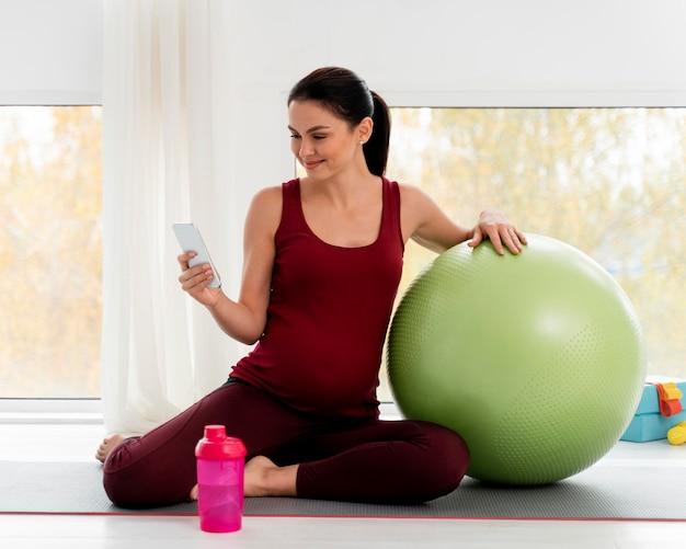 Беременная женщина проверяет свой телефон после тренировки