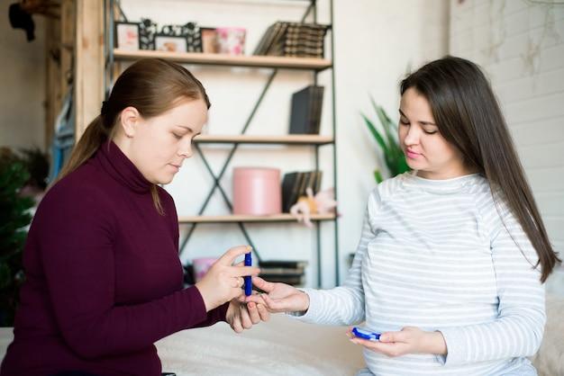 Беременная женщина проверяет уровень сахара в крови, тест на диабет.