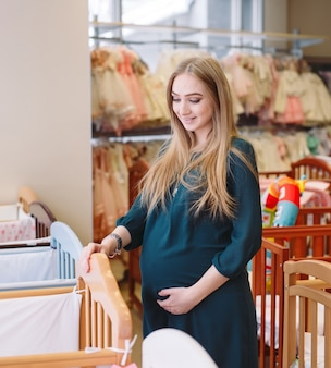 Pregnant woman chooses a baby cot in the store.