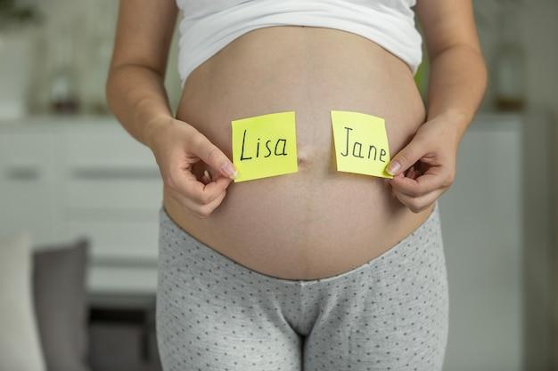 Беременная женщина выбирает имя ребенка на животе