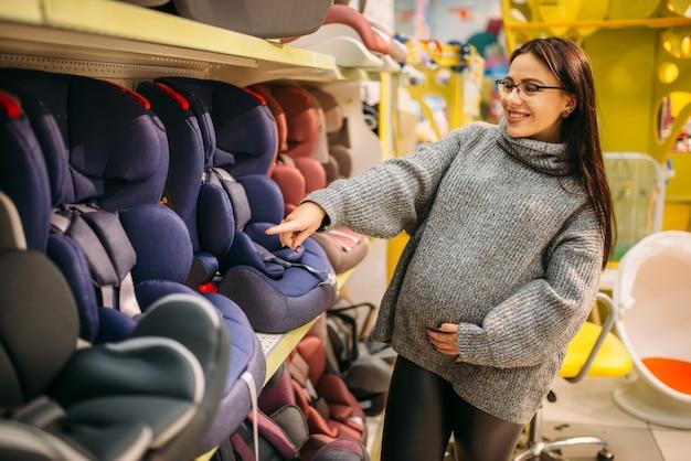 Беременная женщина выбирает детское автокресло в магазине