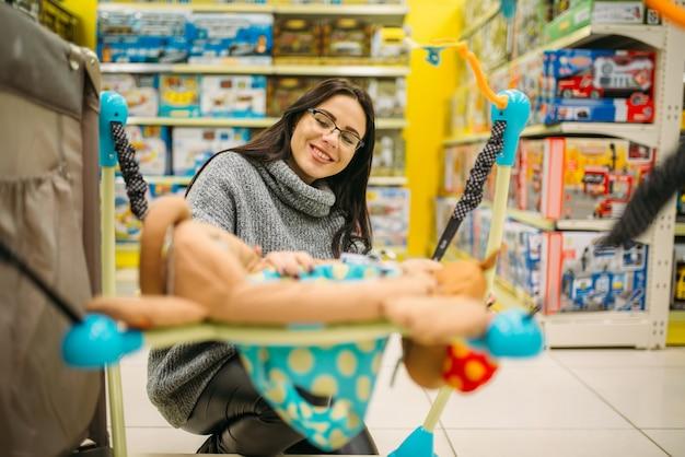 妊娠中の女性が店でハンギングベッドを選択します。
