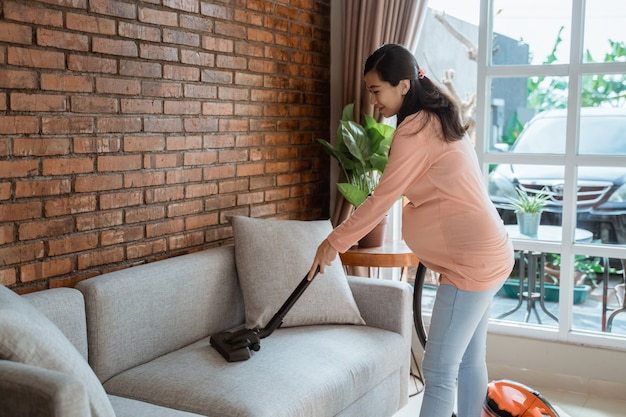 Pregnant woman cleaning couch with vacuum cleaner