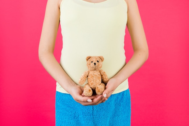 Pregnant woman in colorful home clothing holding teddy bear