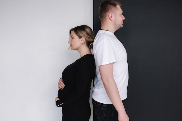 Беременная женщина сравнивает свой живот с пивным животом мужа на черно-белом фоне