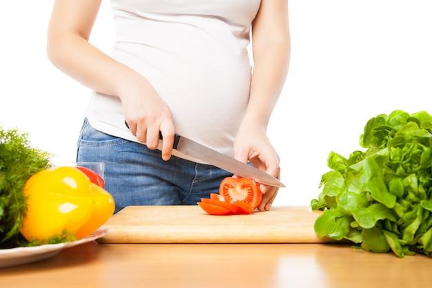Беременная женщина режет помидор на борту крупным планом