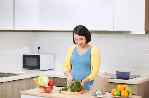 妊娠中の女性が新鮮なグリーンサラダのためにブロッコリーを切る、女性は自宅でおいしいオーガニックディナーを準備します