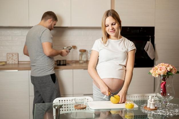 Pregnant woman cutting a lemon