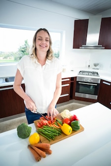 Pregnant woman cutting vegetables in the kitchen