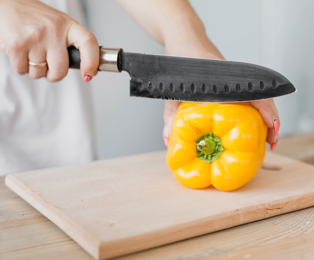 Pregnant woman cutting a yellow pepper