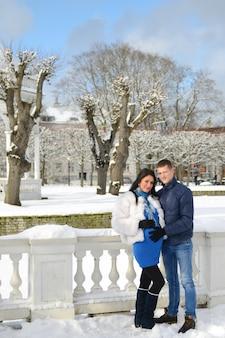 妊娠中の女性は夫とデートし、キスをし、ウィンターパークで一緒に歩きます。冬の街でキス妊娠中のカップル